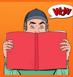 Pop art amazed man holding book vector