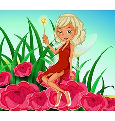 A fairy holding a wand sitting at the red flowers vector image