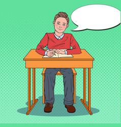 pop art happy schoolboy sitting at school desk vector image vector image