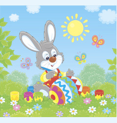little bunny coloring an easter egg vector image