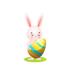 cute easter rabbit on green grass with gold egg vector image