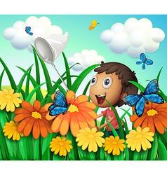 A boy catching butterflies at the flower garden vector
