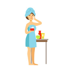 Woman in bath towel is applying cream on her face vector