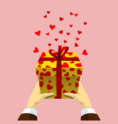 gift box in men hands with flying hearts vector image