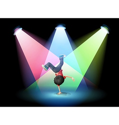 A boy breakdancing at the stage with spotlights vector image