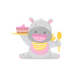 Cute smiling hippo in a bib eating cake with spoon vector