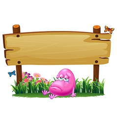 A pink beanie monster under the empty wooden vector image