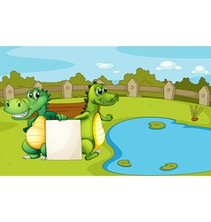 Crocodiles holding an empty banner vector image