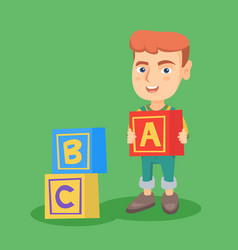 smiling caucasian boy playing with alphabet cubes vector image