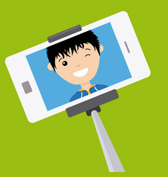 young boy making a photo with stick selfie vector image