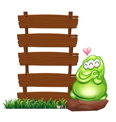 A green monster beside the empty wooden boards vector image vector image