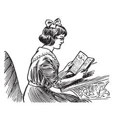 Girl reading a book at a school desk study vector