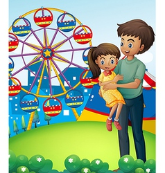 A father with his daughter at the carnival vector image