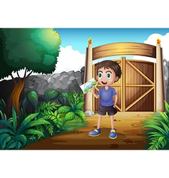 A boy holding a picture inside the gate vector image vector image