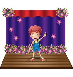 A stage with a young boy waving happily vector