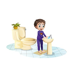 A boy washing his hands at the sink vector image