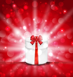 round gift box on light red background with glow - vector image vector image