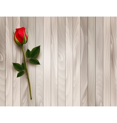Single red rose on a wooden background vector image