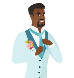 Cheerful african-american groom adjusting tie vector