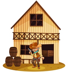 A man holding a gun in front of a wooden house vector