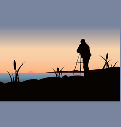 Photographer at sunset vector