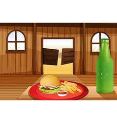 A burger and fries in a red plate and a bottle of vector