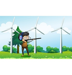 A boy shooting in front of the windmills vector