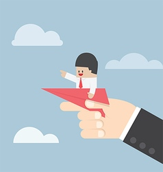 Businessman sitting on paper plane with big hand r vector image