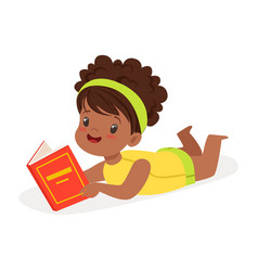 Sweet african girl lying on the floor and reading vector