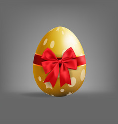 Realistic golden easter egg tied of red ribbon vector