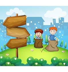 Two boys playing sack race near the arrow boards vector image vector image