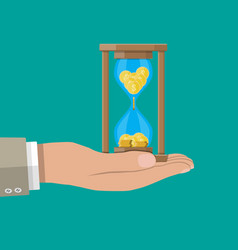 old hourglass clocks with coins inside in hand vector image
