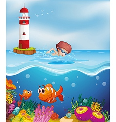 A boy swimming with fishes and corals at the beach vector image