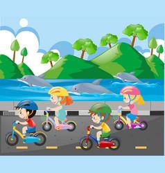 Children riding bike along the ocean vector