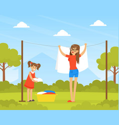 mother and daughter hanging wet clothes out to dry vector image