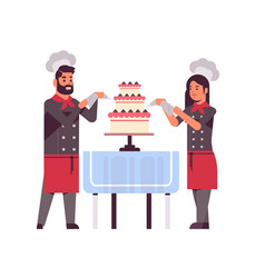 Cooks couple professional pastry chefs decorating vector