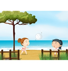 Two little girls playing volleyball at the beach vector image