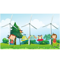 Two girls hanging their clothes near the windmills vector image vector image