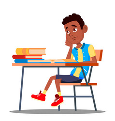 Sad child sitting at a desk in the classroom vector