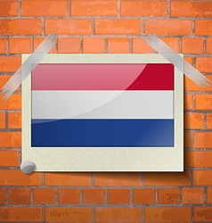 Flags Netherlands scotch taped to a red brick wall vector