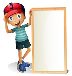 A young boy standing beside an empty signboard vector image