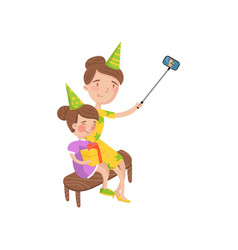 Mother and her daughter wearing party hats taking vector