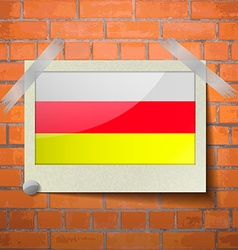 Flags North Ossetia scotch taped to a red brick vector