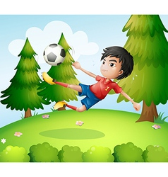 A boy playing soccer near the pine trees vector image