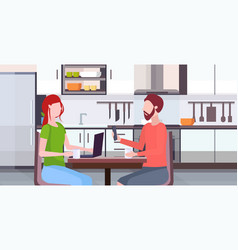 Couple sitting at table woman using laptop man vector