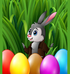 Easter bunny and colorful eggs in the grass bushes vector