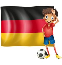 A boy with a soccer ball in front of the flag of vector image