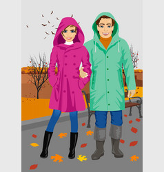 young couple wearing raincoats in park in autumn vector image vector image