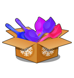 cardboard box with colored plastic shovels vector image