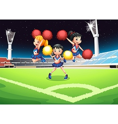 Three cheerdancers performing in the soccer field vector image vector image